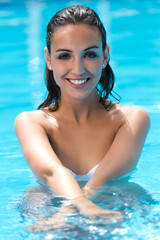 Beautiful girl posing in the swimming pool.