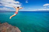 Fototapety Man jumping off cliff into the ocean