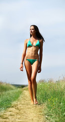 Young slim model in a green bikini walking on rural path