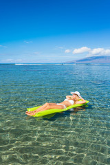 Woman floating on raft in tropical ocean