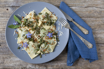 handmade pasta ravioli with borage, flowers and sage on plate