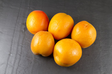 Five sun sweet apricots, one halved with stone. Prunus.