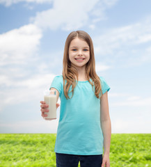 smiling little girl giving glass of milk