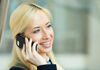 Happy woman talking on phone background corporate office windows