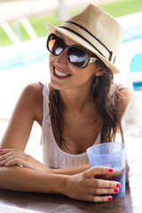 Beautiful girl drinking in the pool bar.