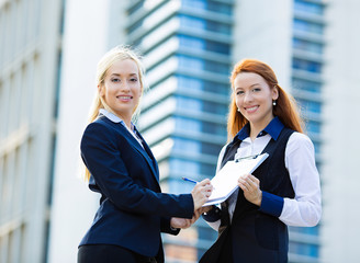 Businesswomen signing contract document, corporate office