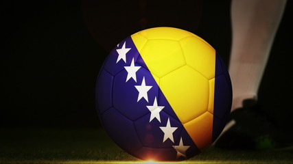 Football player kicking bosnia flag ball