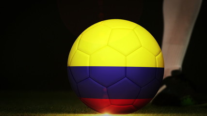 Football player kicking colombia flag ball