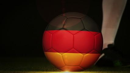 Football player kicking germany flag ball