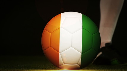 Football player kicking ivory coast flag ball