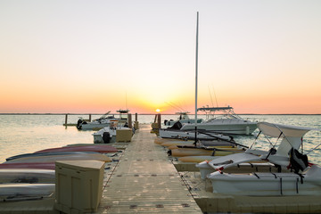boats moored to pier at sundown