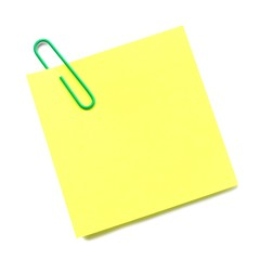 Blank post it note with green paper clip isolated on white