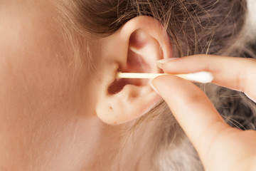 woman cleans her ear using cotton swab