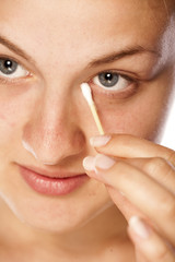 beautiful young woman cleans her eye using cotton swab