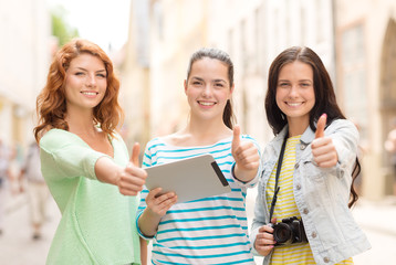 smiling teenage girls with tablet pc and camera