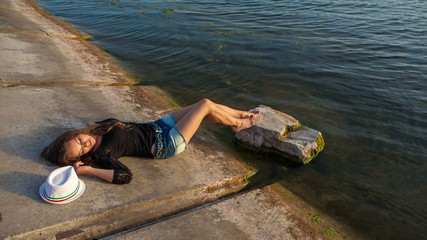 Luxurious young girl in short shorts lying near the water
