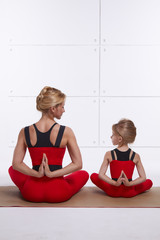 Mother and daughter yoga exercise in comfortable tracksuits