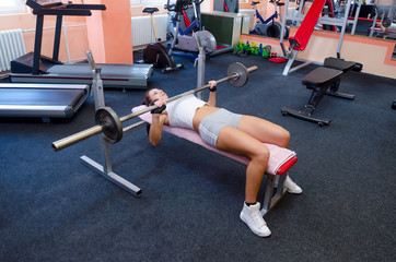 Beautiful girl lifting weights in the gym