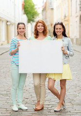 smiling teenage girls with blank billboard