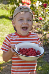 Little boy with bowl of raspberry