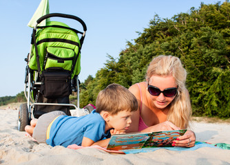 Mother and son sitting on sandy beach reading a book together