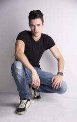 Handsome young man sitting on light background