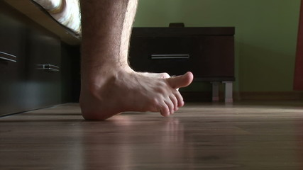 Male feet getting out of bed