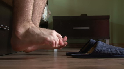 Male feet getting out of bed, put on slippers