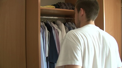 Man choosing shirt from wardrobe