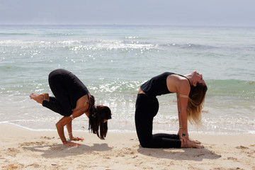 Stock image of women performing yoga poses on the beach