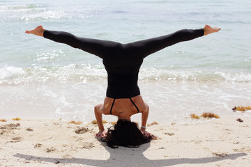 Headstand leg split on the beach stock image