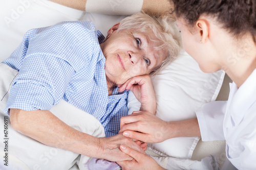 Leinwanddruck Bild Elderly woman in bed