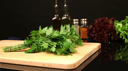Bunch of parsley falls on chopping board