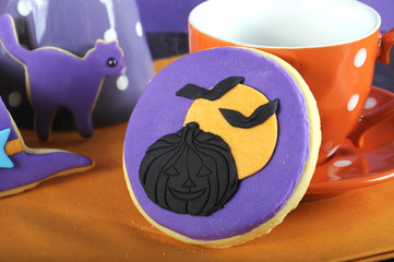 Happy Halloween trick or treat purple and orange cookie close up