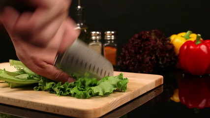 Man chopped lettuce on a cutting board on the kitchen table