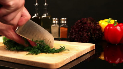 Man chopped dill on a cutting board on the kitchen table