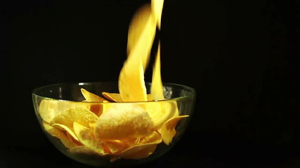 SLOW: Potato chips falling in a transparent bowl