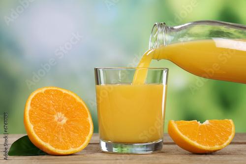 canvas print picture Orangensaft eingießen in ein Glas