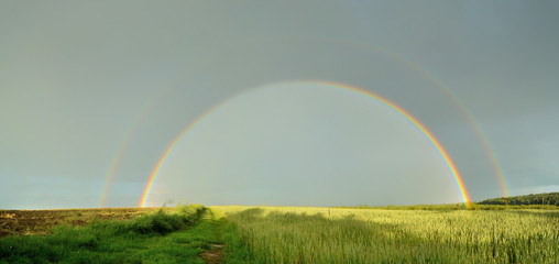 Panorama of double full rainbow over country road.