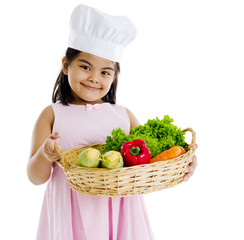 Little indian girl holding a basket of vegetables