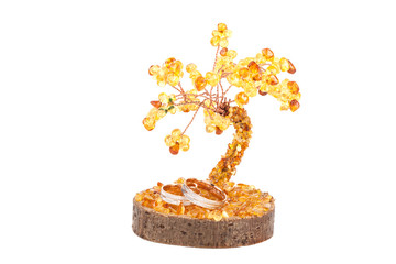 Amber tree of happiness and wedding rings isolated on white back