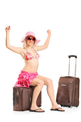 Joyful woman sitting on her baggage