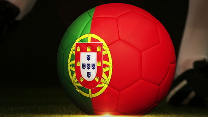Football player kicking portugal flag ball