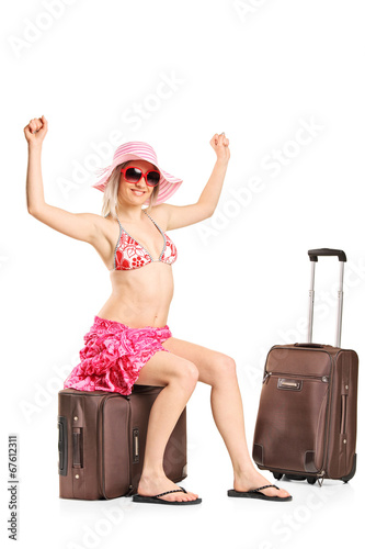 Joyful woman sitting on her baggage