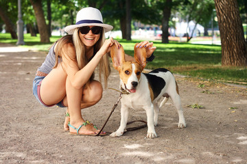 happy young woman playing with Beagle dog outdoors . funny shot