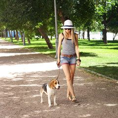 young  woman walking her beagle dog in the green park
