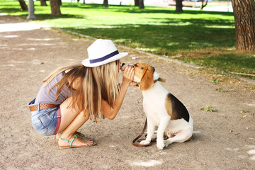 girl kissing her beagle dog in nature outdoors.