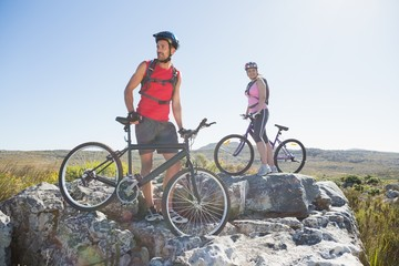 Fit cyclist couple standing at the summit looking around