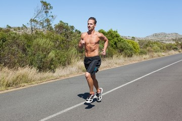 Shirtless man jogging on open road