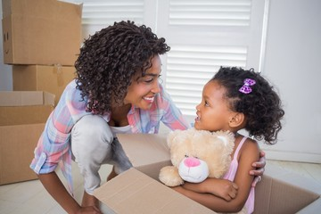 Cute daughter sitting in moving box holding teddy with mother